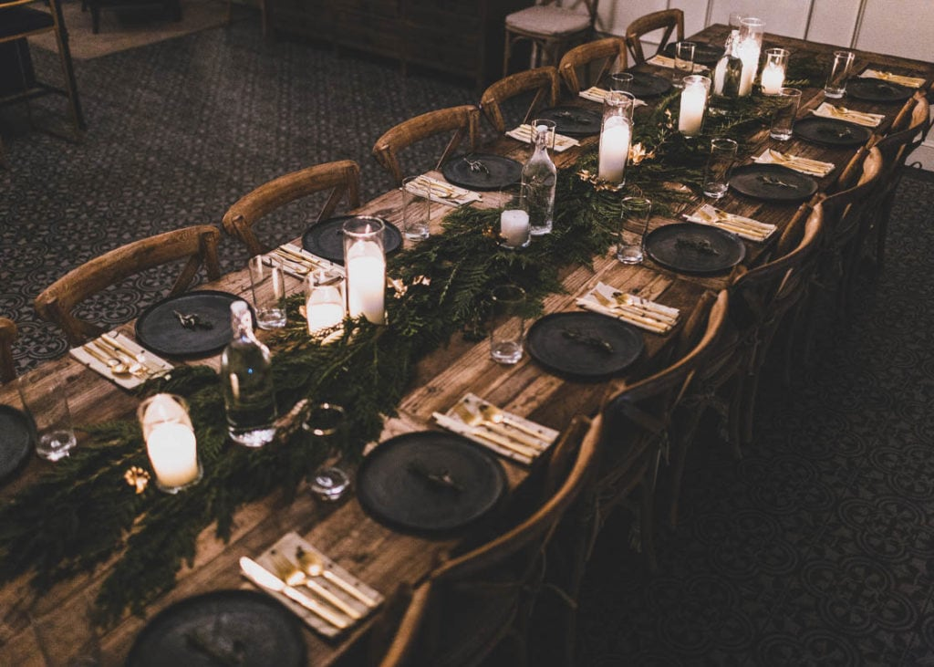 Scrap Supper tablescape using foraged cedar and rosemary by Rachelle Hacmac. Angled photo.