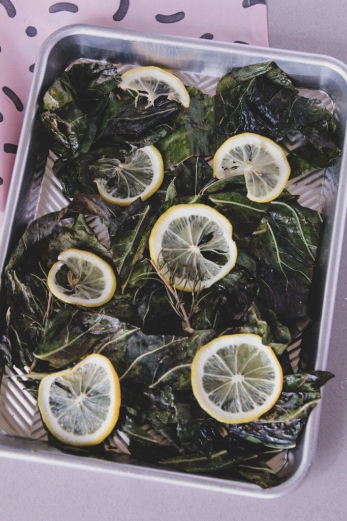 roasted cauliflower leaves and lemon on a tray