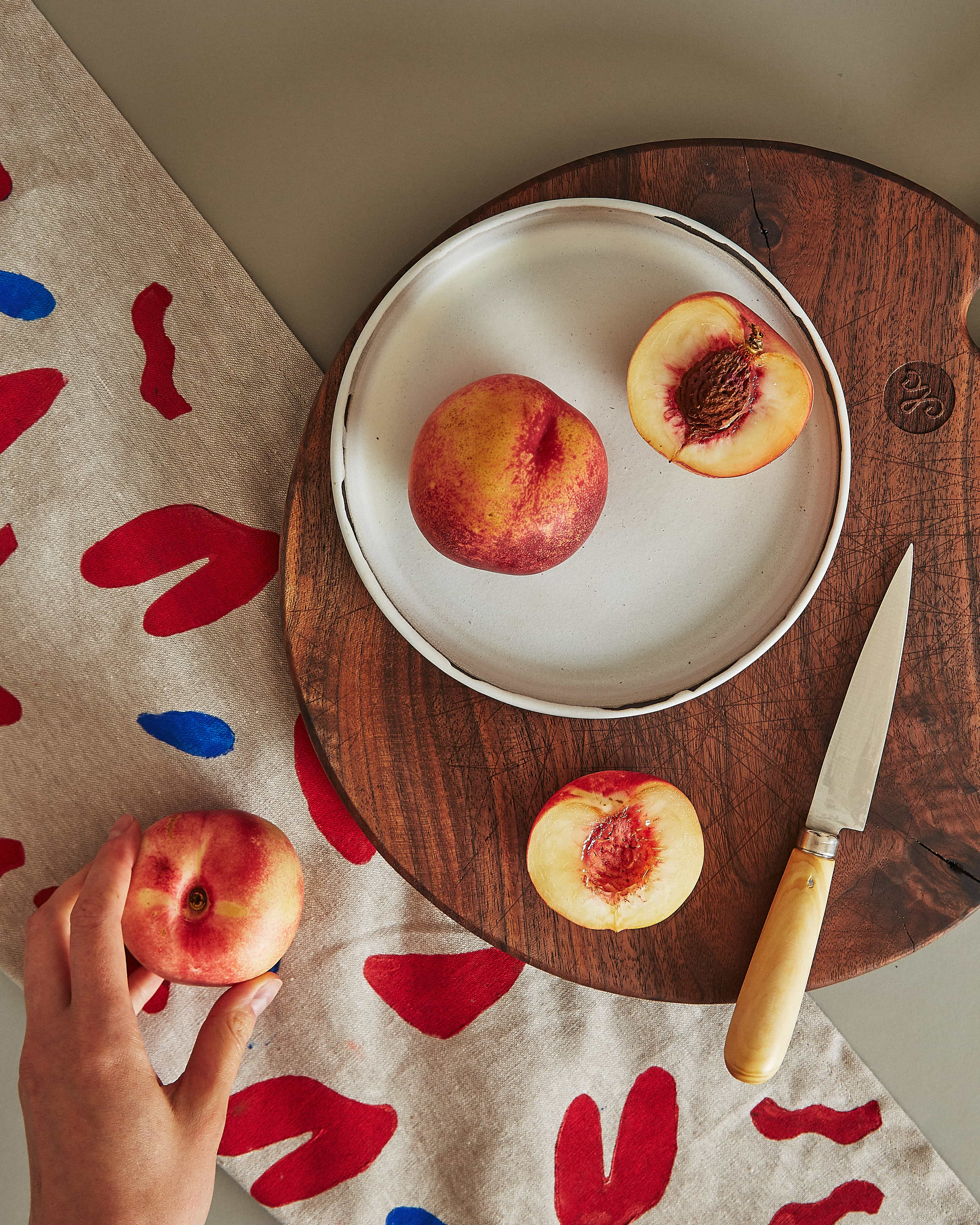 reclaimed, round walnut cutting board, with peaches and tea towel