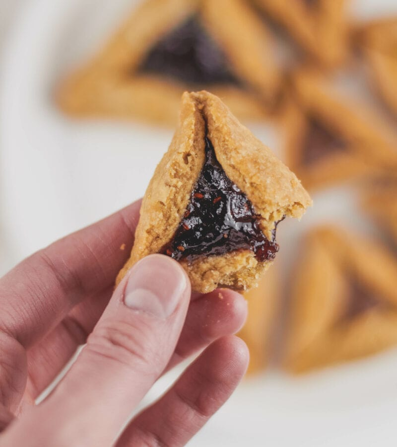 holding a vegan hamantaschen with jelly and a corner bitten off