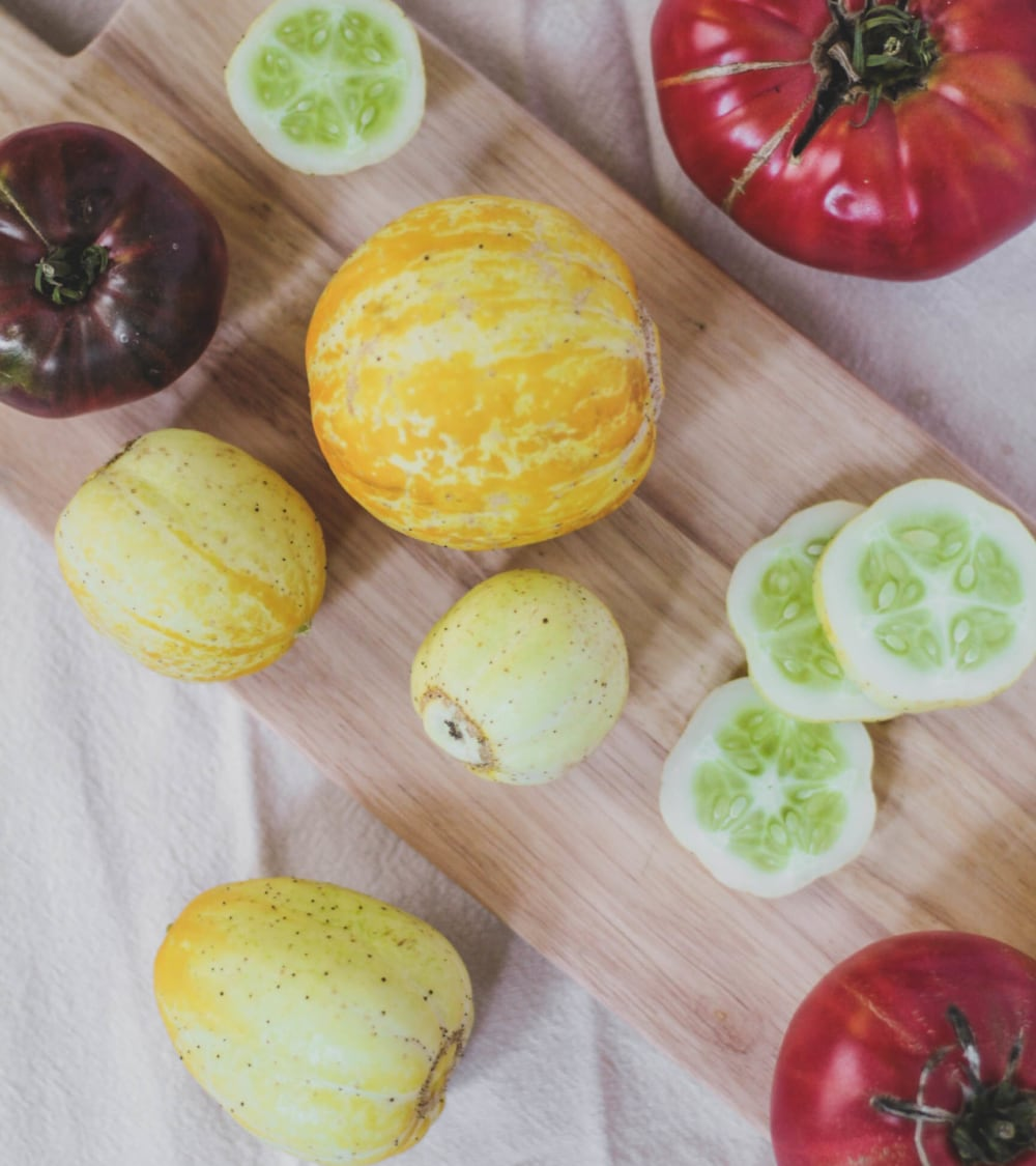 Lemon Cucumbers and Heirloom Tomatoes on cutting board